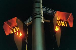 Crosswalk signs appear on opposite sides of a traffic light pole.